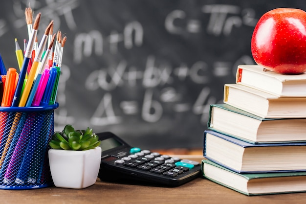 Books and stationery at teacher desk Free Photo