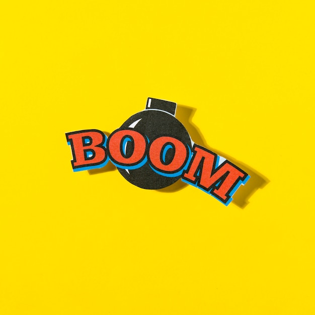 Boom comic text speech bubble with bomb on yellow background Free Photo