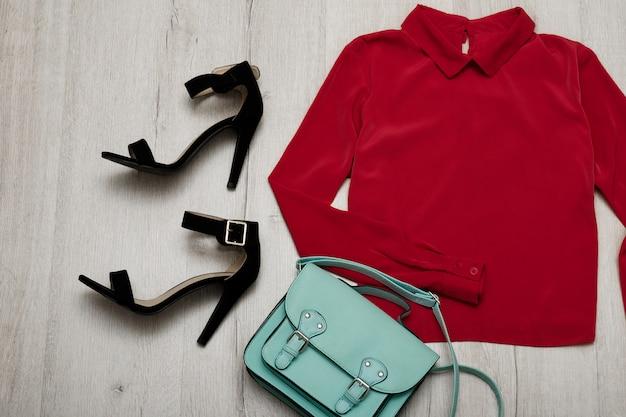 Bordeaux blouse, black shoes, handbag. fashionable concept. wooden background Premium Photo