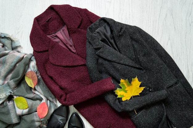 Bordeaux and gray coats, scarf, black shoes and autumn leaves. fashionable Premium Photo