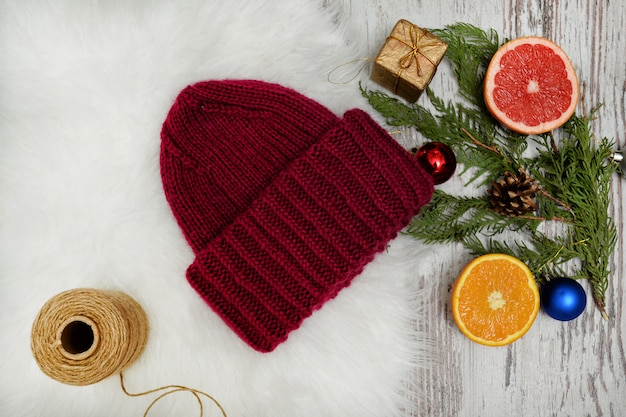 Bordeaux hat, spruce branch, christmas tree decorations and citrus. new year's concept. Premium Photo