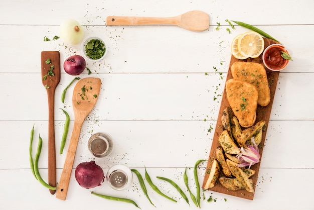 Border arranging from cooking utensils and ready meal on wooden desk Free Photo