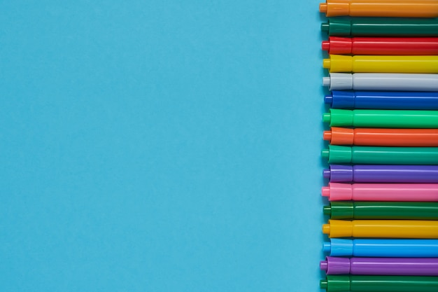 Border of colored felt tip pens on blue background with copyspace Premium Photo