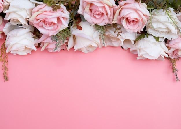 ピンクの背景にパステルピンクのバラの花で作られた枠 Premium写真