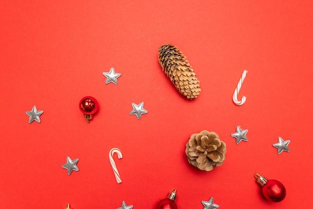 소나무 콘, 크리스마스 장식은 별, 빨간색 배경에 사탕 지팡이와 빨간색으로 만든 테두리입니다. 프리미엄 사진