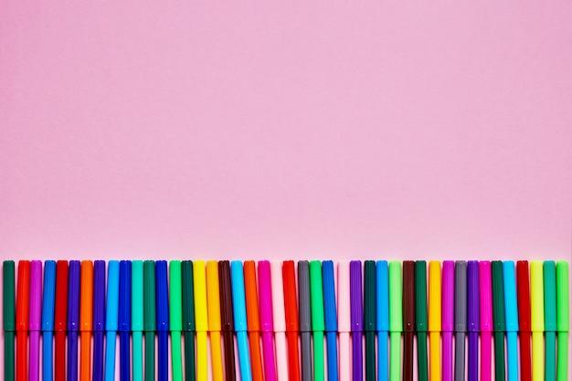 Граница цветных фломастеров на розовом фоне с местом для текста. Premium Фотографии