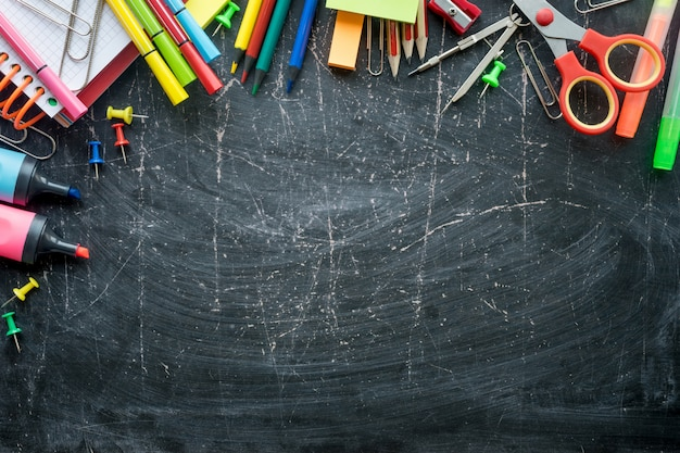Border of school supplies on a chalkboard background. free space Premium Photo
