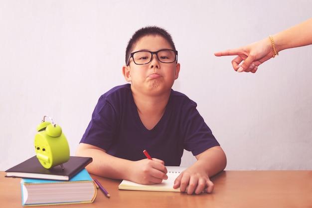 Пробуренный и утомленный азиатский мальчик студента делая домашнюю работу. сердитая мать указывает на него Premium Фотографии