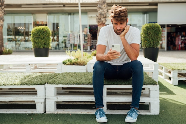 Bored bearded man checking his phone Free Photo
