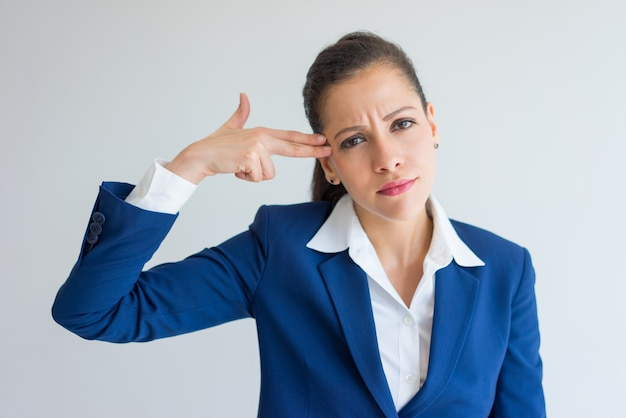 Bored business woman showing gun shot and suicide gesture. Free Photo