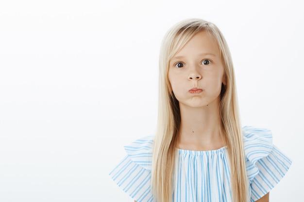 Bambina annoiata e spensierata che cerca di rallegrarsi, scherzare. ritratto di giocoso adorabile giovane femmina con capelli biondi, imbronciato, trattenendo il respiro e fissando con gli occhi schioccati Foto Gratuite