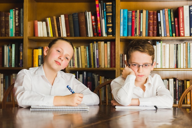 Bored children sitting in library with notebooks Free Photo