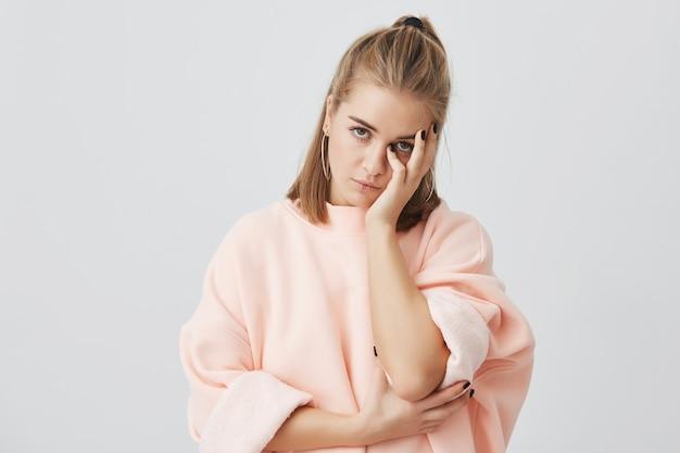 面白くないピンクのスウェットシャツを着て、顔を手で触ってうんざりして、面白くない話を聞いてうんざりしている退屈なヨーロッパの女子学生ボディランゲージ 無料写真