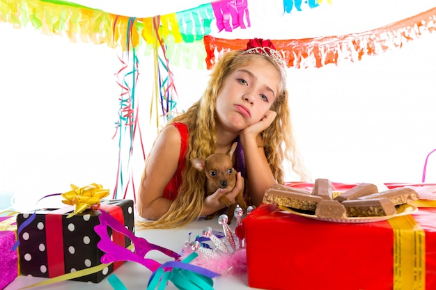 Bored gesture blond kid girl in party with puppy Premium Photo