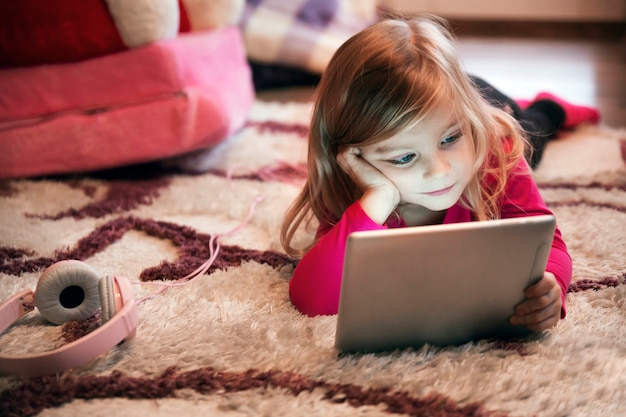 Bored girl using tablet on carpet Free Photo