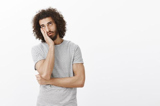 Annoiato indifferente bell'uomo ispanico con barba e acconciatura afro, facendo il palmo della faccia e alzando lo sguardo con espressione stanca e stufo Foto Gratuite