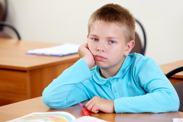 Bored little boy at his desk Free Photo
