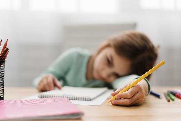 Bambina annoiata che riposa la testa mentre fa i compiti Foto Gratuite