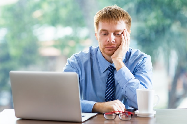 Bored man looking at a laptop Free Photo