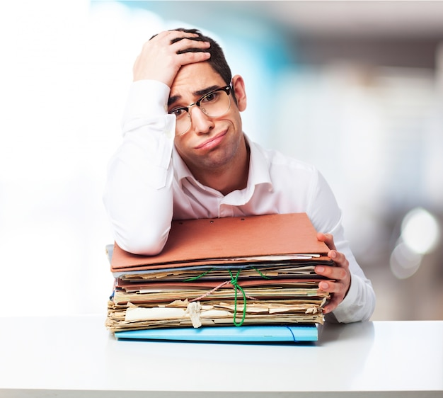 Bored man looking at a pile of papers with one hand on his forehead Free Photo