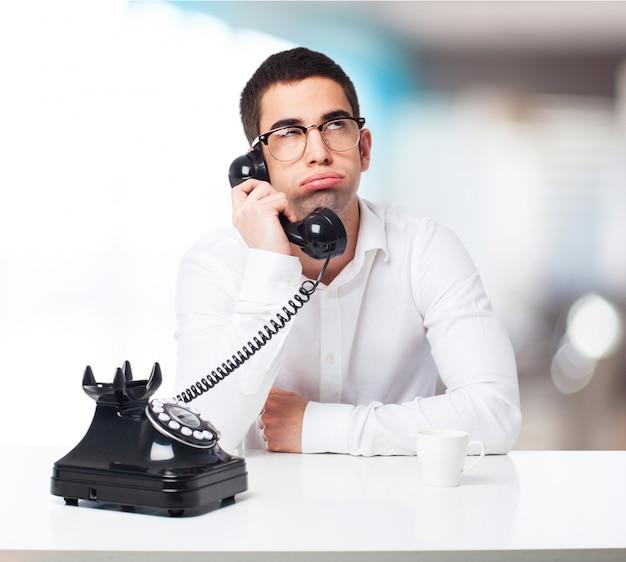 Bored man talking on a black phone Free Photo
