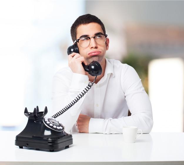 Bored man talking on the phone Free Photo