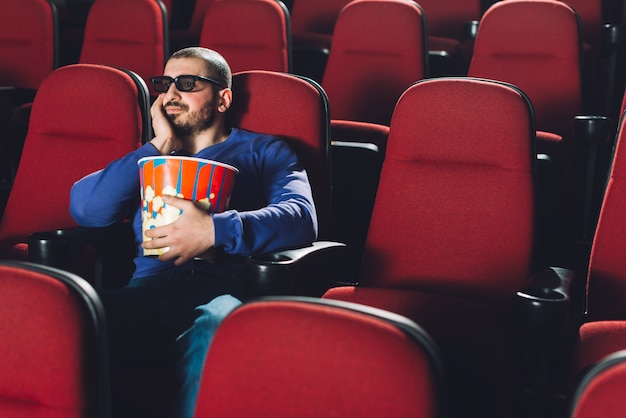 Bored man watching movie in cinema Free Photo