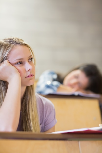 Bored student listening while classmate sleeping in university Premium Photo