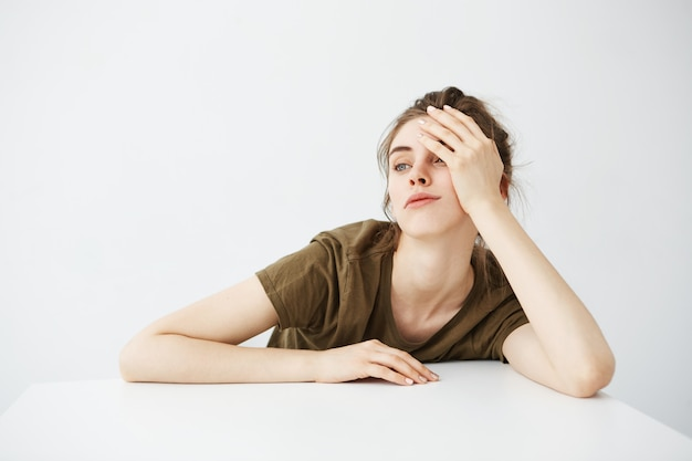 Bored tired dull young woman student with bun sitting at table over white background. Free Photo