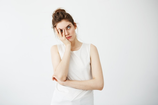 Fronte nascondentesi della giovane donna graziosa stanca annoiata dietro le mani. Foto Gratuite