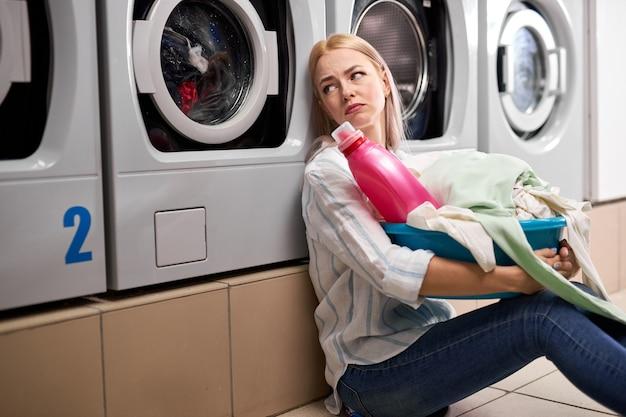 汚れた服と洗剤のピンクのボトルを洗面器に持っている退屈な女性は、洗濯機に寄りかかって床に座って、一人で落ち込んで、洗濯場に座っています Premium写真