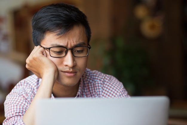 Bored young asian male student sitting at laptop Free Photo