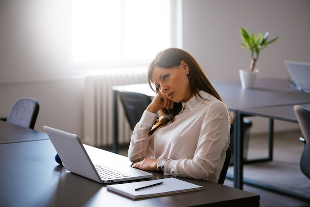 Bored young woman in the office working with a laptop Premium Photo