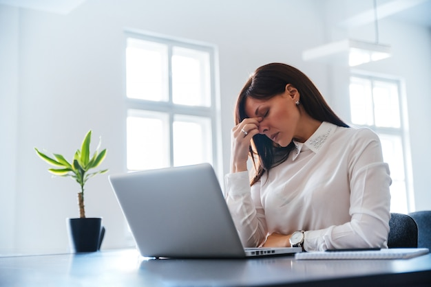 Bored young woman in the office working with a laptop. Premium Photo