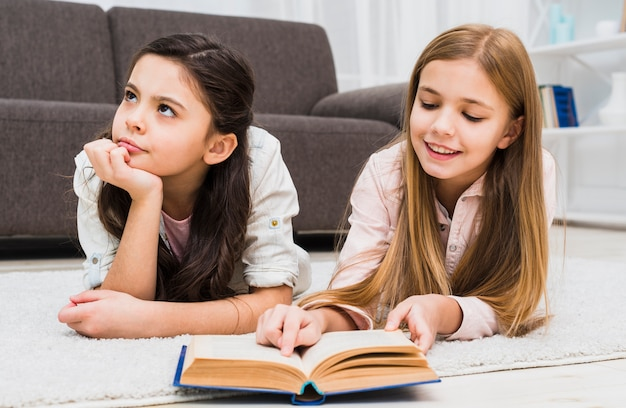 Boredom girl lying with her friend reading book in the living room Free Photo