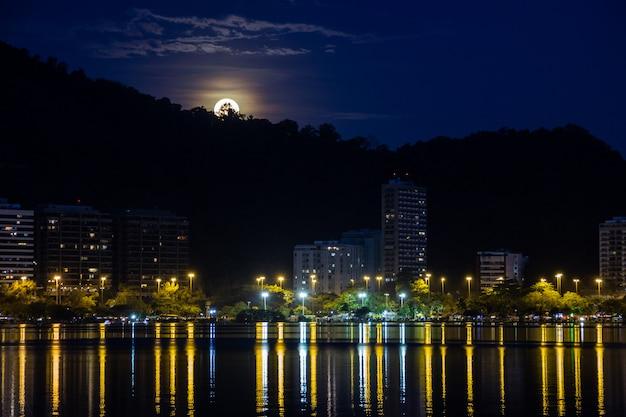 Born of the full moon, in lagoon rodrigo de freitas in rio de janeiro. Premium Photo