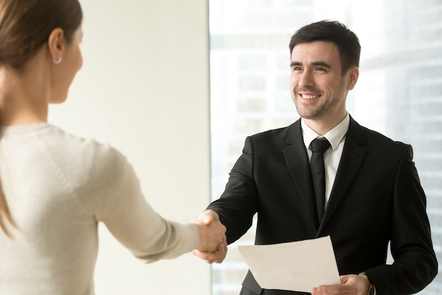 Boss congratulating female employee with promotion Free Photo