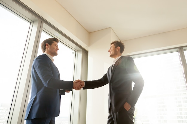 Boss shaking hand and thanking worker for good job Free Photo