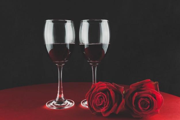 Botella de vino con dos copas y una rosa encima de una mesa Free Photo