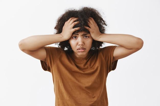 悩まされて疲れて落ち込んでいるアフリカ系アメリカ人女性のアフロの髪型はイライラし、頭に顔をしかめ、髪に手をつないで悩んで疲れている 無料写真