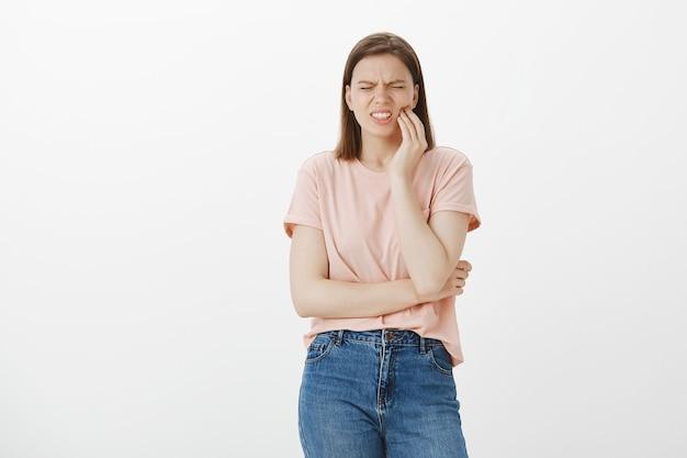 Обеспокоенная милая женщина гримасничает от боли и трогает щеку, жалуется на зубную боль, нужен стоматолог Бесплатные Фотографии