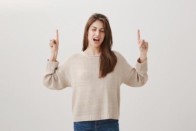 Обеспокоенная женщина, выражающая сожаление, показывая пальцем вверх и разочарованно вздыхая Бесплатные Фотографии