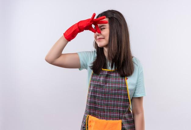 Giovane bella ragazza infastidita che indossa grembiule e guanti di gomma chiudendo il naso tra gli occhi chiusi Foto Gratuite