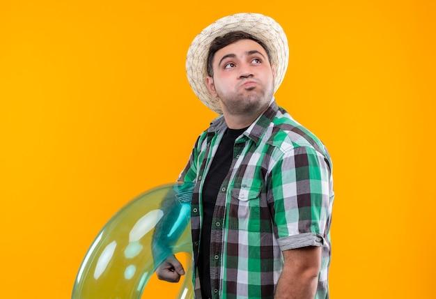 オレンジ色の壁の上に立っている吹く頬を脇に見て膨らませてリングを保持しているチェックシャツと夏の帽子で悩まされている若い旅行者の男 無料写真