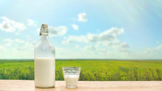 緑の牧草地と青い空を背景に新鮮なミルクとボトルとグラス。スペースをコピーします。ワイドバナー Premium写真