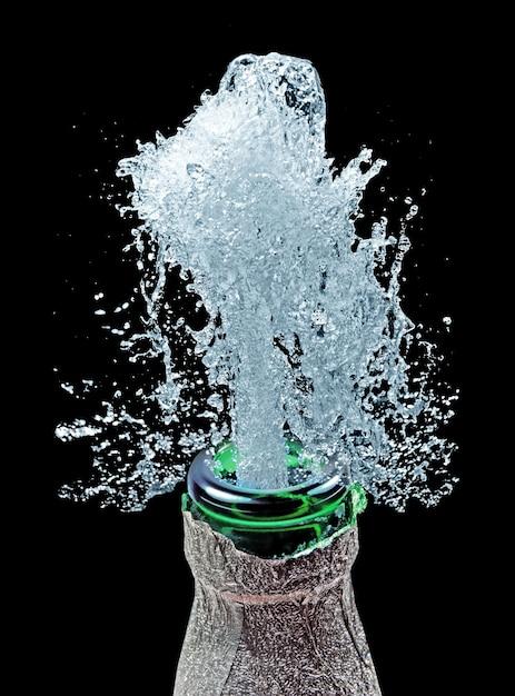 Бутылка и брызги воды на черном Premium Фотографии