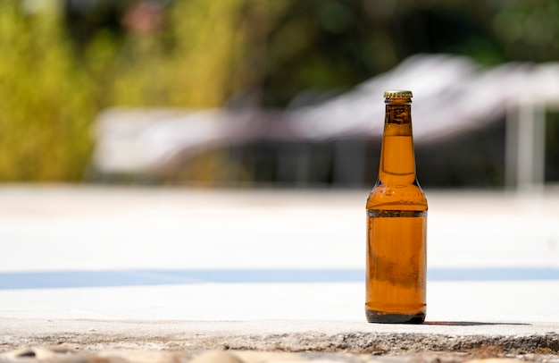 Bottle of beer on the edge of a swimming pool. Premium Photo