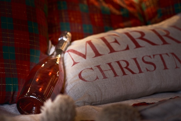 Bottle of champagne in bed. christmas party. pillow with the inscription merry christmas. Premium Photo