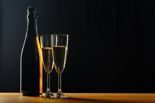 Bottle of champagne and glasses over dark Premium Photo