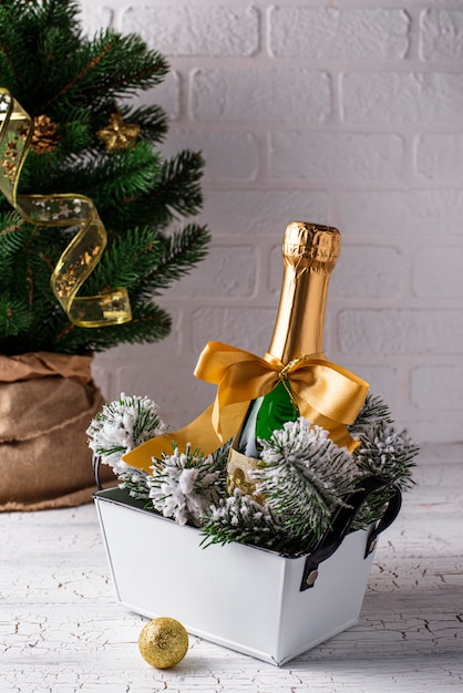 Bottle of champagne in a gold wrapper with christmas decoration Premium Photo